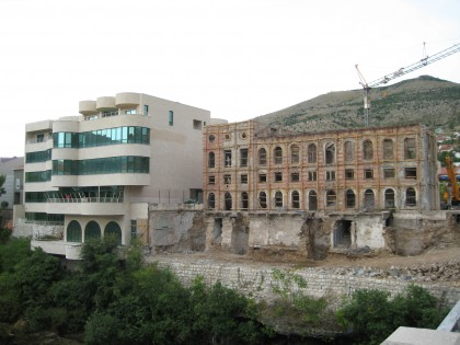 A ruined building from the war next to a new building in Mostar